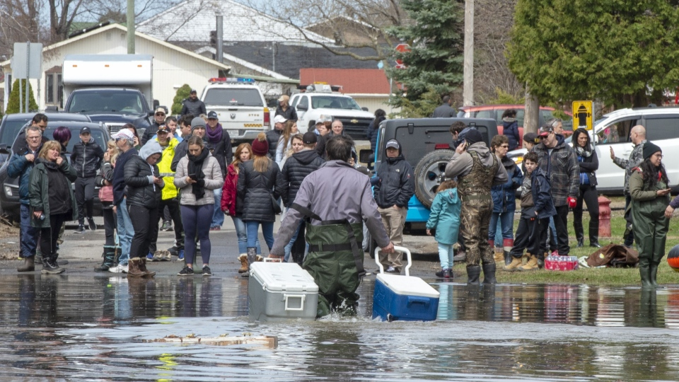 Residents carry their belongings through flooded streets after a dike broke causing widespread flooding and forcing thousands of people to evacuate Sunday, April 28, 2019 in Ste.Marthe-sur-la-Lac, Que.(THE CANADIAN PRESS/Ryan Remiorz)
