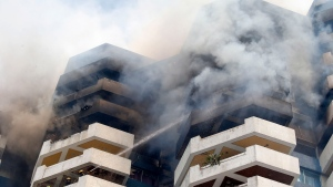 Firemen train their hose on fire in the top floors of a 21-story Pacific Coastal Plaza condominium Monday, April 29, 2019, in Manila, Philippines. (AP Photo/Bullit Marquez)