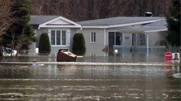 A garbage bin floats in flooded streets in Sainte Marthe sur le Lac