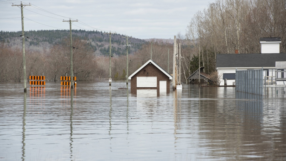 The Darlings Island Road, left, is submerged by the flood waters of the St. John River in Nauwigewauk, New Brunswick, on April 26, 2019. (Stephen MacGillivray / THE CANADIAN PRESS)