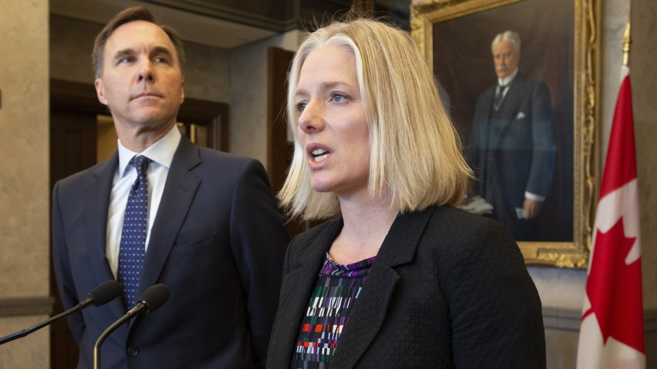 Minister of Finance Bill Morneau looks on as Minister of Environment and Climate Change Catherine McKenna speaks in the foyer of the House of Commons in Ottawa, Monday April 29, 2019. THE CANADIAN PRESS/Adrian Wyld