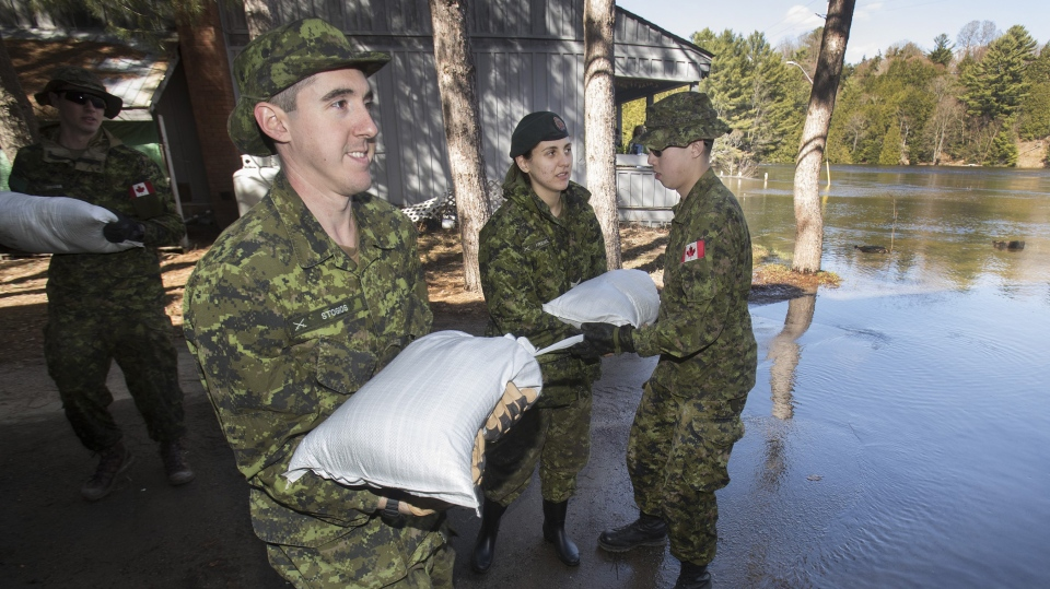 Soldiers from Queen's York Rangers in Aurora sandbag an apartment building along the Muskoka River in Bracebridge Ont., Sunday, April 28, 2019. THE CANADIAN PRESS/Fred Thornhill