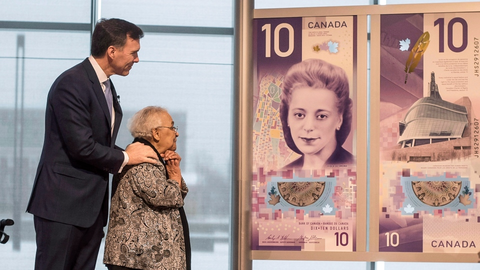 Wanda Robson, second from left, sister of Viola Desmond, admires the new $10 bank note featuring Desmond with Finance Minister Bill Morneau during a press conference in Halifax on Thursday, March 8, 2018. (THE CANADIAN PRESS / Darren Calabrese)