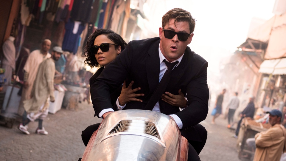 "This image released by Sony Pictures shows Chris Hemsworth, foreground, and Tessa Thompson in a scene from Columbia Pictures' ""Men in Black: International."" (Giles Keyte/Sony/Columbia Pictures via AP)"