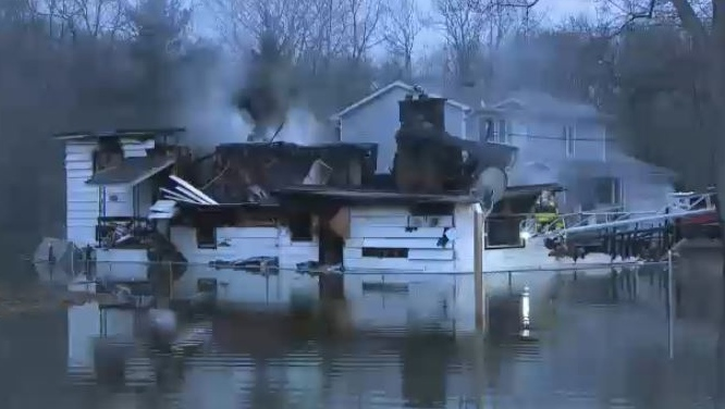A home in Constance Bay, Ont. that was already surrounded by flood waters caught fire overnight.