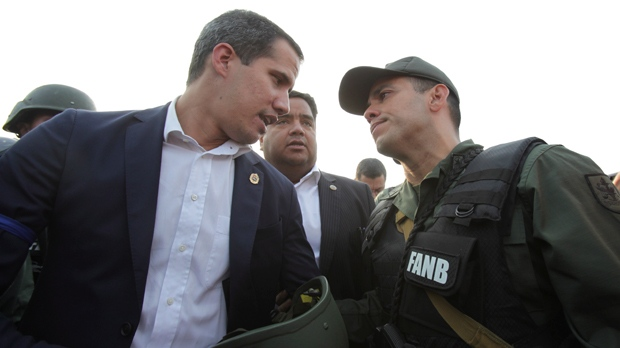 Venezuela's opposition leader and self proclaimed president Juan Guaido talks to an Army officer outside La Carlota air base in Caracas, Venezuela, Tuesday, April 30, 2019. Guaido took to the streets with a small contingent of armed soldiers and detained activist Leopoldo Lopez calling for a military uprising. (AP Photo/Boris Vergara)