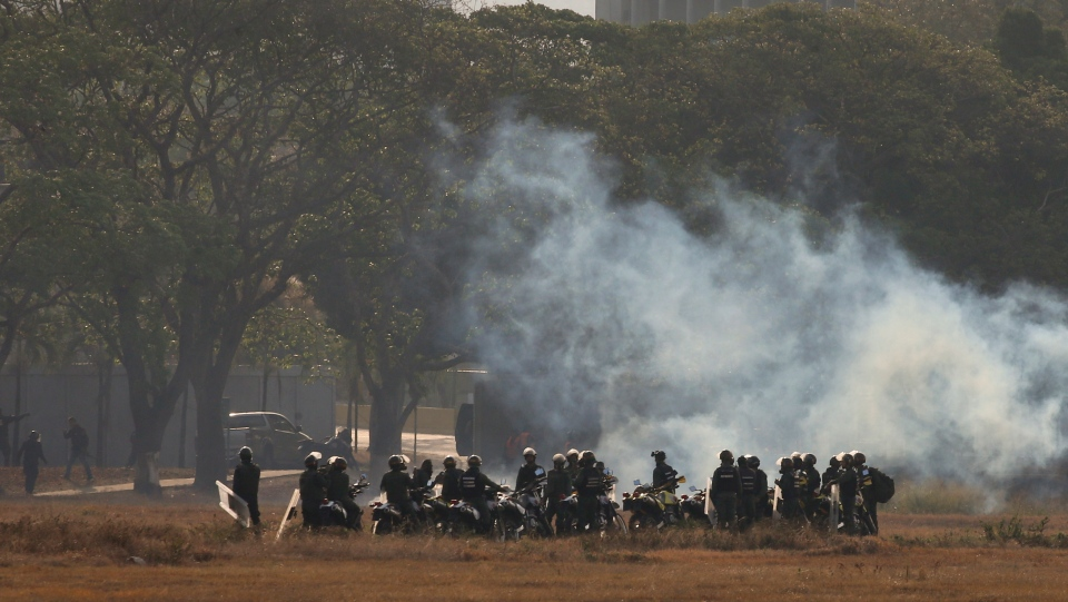 Troops loyal to Venezuela's President Nicolas Maduro stand amid tear gas they fired from inside La Carlota air base, toward a crowd of a few hundred civilians and a small group of rebel soldiers gathered outside the base in Caracas, Venezuela, Tuesday, April 30, 2019. (AP Photo/Fernando Llano)