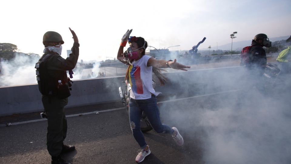 An opponent to Venezuela's President Nicolas Maduro high fives a rebel soldier on a highway overpass outside La Carlota air base amid tear gas fired by loyalist soldiers inside the base in Caracas, Venezuela, Tuesday, April 30, 2019. (AP Photo/Boris Vergara)