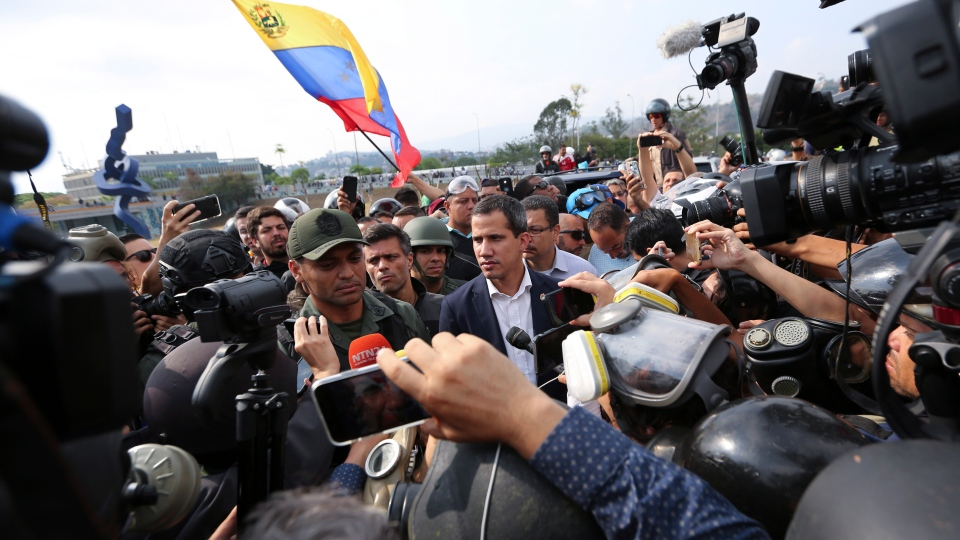 Venezuela's opposition leader and self-proclaimed president Juan Guaido, centre, stands with an unidentified military officer who is helping to lead a military uprising, center left, as they talk to the press and supporters outside La Carlota air base in Caracas, Venezuela, Tuesday, April 30, 2019. (AP Photo/Fernando Llano)