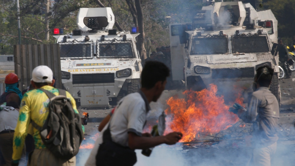 Opponents to Venezuela's President Nicolas Maduro face off with Bolivarian National Guards in armored vehicles who are loyal to the president, during an attempted military uprising in Caracas, Venezuela, Tuesday, April 30, 2019. (AP Photo/Ariana Cubillos)