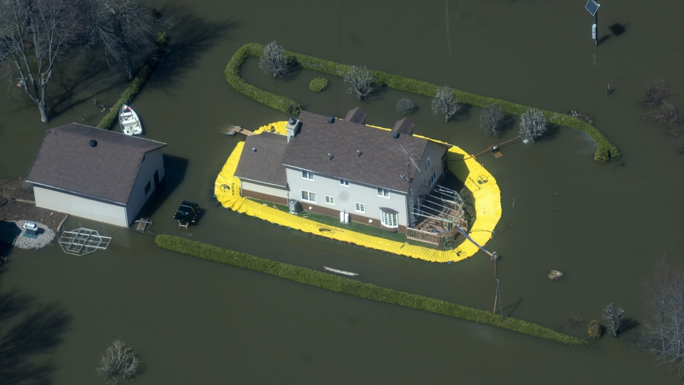 A temporary dike protects a house in a flooded neighbourhood in Rigaud, Que. on Tuesday, April 30, 2019. THE CANADIAN PRESS/Paul Chiasson