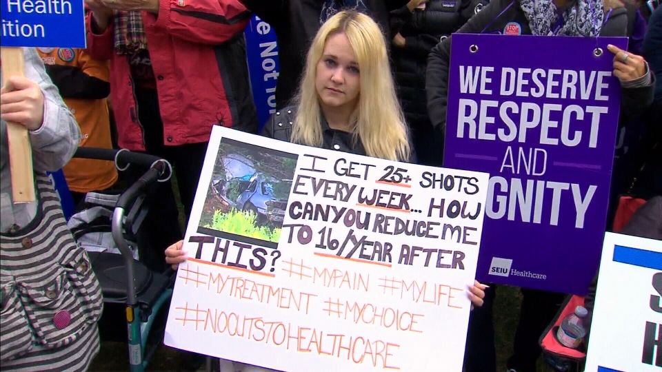 Brittany Rollin sits outside Queen's Park to protest the government's changes to the health care system on April 30, 2019.