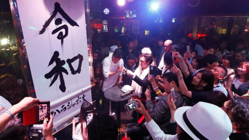 People take a photo of 'Reiwa,' new Emperor Naruhito's era's name, during a countdown event at Maharaja Roppongi, at midnight Wednesday, May 1, 2019, in Tokyo, Japan. (Yohei Fukai/Kyodo News via AP)