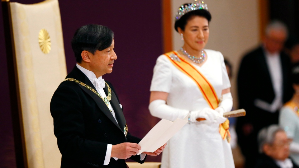 Japan's new Emperor Naruhito, accompanied by new Empress Masako, makes his first address during a ritual after succeeding his father Akihito at Imperial Palace in Tokyo, Wednesday, May 1, 2019. (Japan Pool via AP)