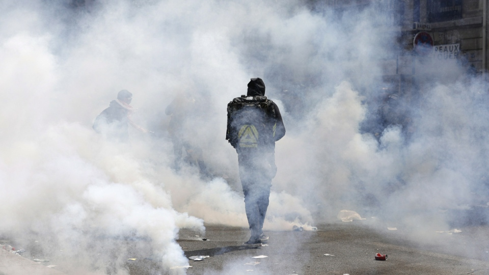 A protester walks through a cloud of tear gas during a May Day demonstration in Paris, on May 1, 2019. (Kamil Zihnioglu / AP)