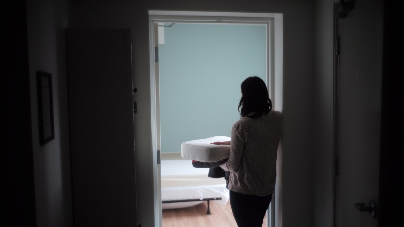 A staff member carries bedding in one of the suites at Toronto's Interval House, an emergency shelter for women in abusive situations, on Monday February 6, 2017.  THE CANADIAN PRESS/Chris Young