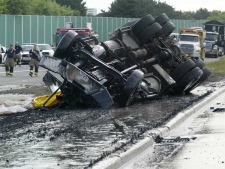 A tanker truck carrying hot tar traveling west-bound on the 401 at Keele, slid out of control on a corner and flipped on July 23, 2007.(CP / Toronto Star / Tory Zimmerman)
