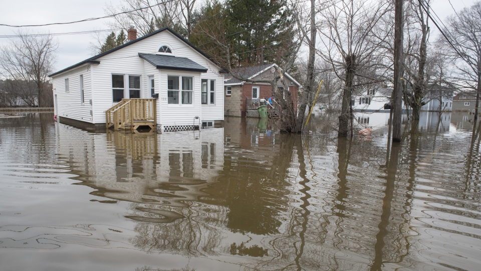 Homes are surrounded by the flood waters on Riverside Drive in Fredericton on Monday April 22, 2019. (THE CANADIAN PRESS/Stephen MacGillivray)