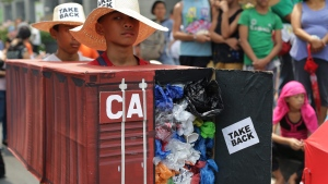 Filipino environmental activists wear a mock container vans filled with garbage to symbolize the 50 containers of waste that were shipped from Canada to the Philippines, as they hold a protest outside the Canadian embassy at the financial district of Makati, south of Manila, Philippines on Thursday, May 7, 2015. THE CANADIAN PRESS/AP, Aaron Favila