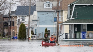 Two men paddle along Jacques-Cartier Street past sandbagged and flooded homes in Gatineau on Thursday May 2, 2019. THE CANADIAN PRESS/Adrian Wyld