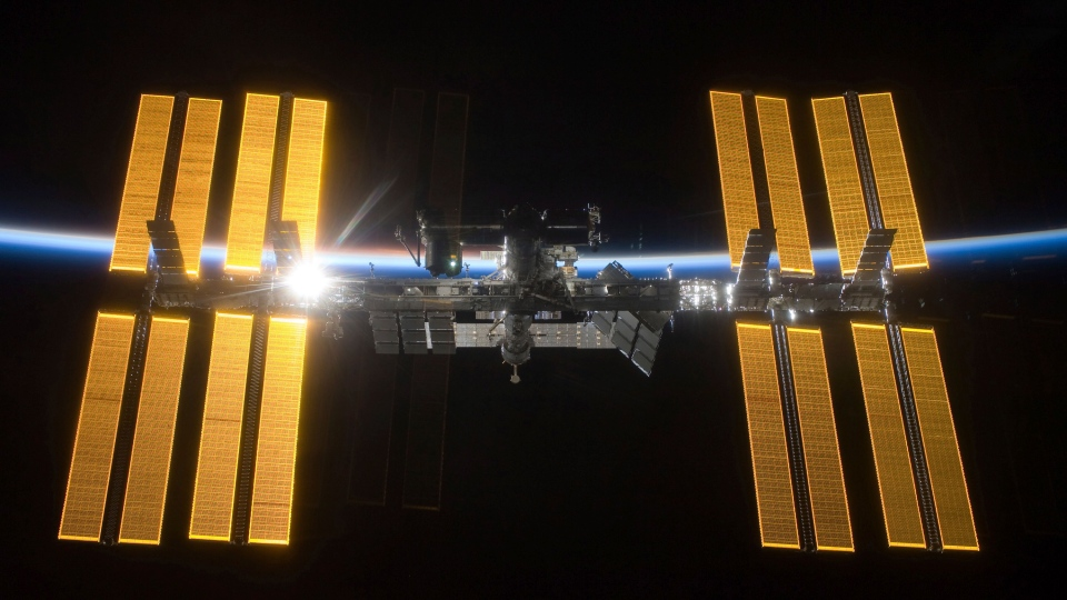 This March 25, 2009 photo provided by NASA shows the International Space Station seen from the Space Shuttle Discovery during separation. In the background is Earth's atmosphere seen as a blue arc. (NASA via AP)
