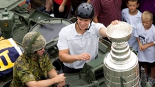 Pittsburgh Penguins captain Sidney Crosby displays the Stanley Cup on an army light armoured vehicle after a flight on a Sea King helicopter in Halifax on Friday, Aug. 7, 2009. (Andrew Vaughan / THE CANADIAN PRESS)