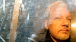 Buildings are reflected in the window as WikiLeaks founder Julian Assange is taken from court, where he appeared on charges of jumping British bail seven years ago, in London, Wednesday May 1, 2019. (AP Photo/Matt Dunham)