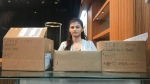 Olivia Gharakhanian poses in front of boxes she says contained 'ICBC papers, void cheques, bank account numbers, first names, last names, and addresses.' (Jazz Sanghera / CTV News Vancouver)
