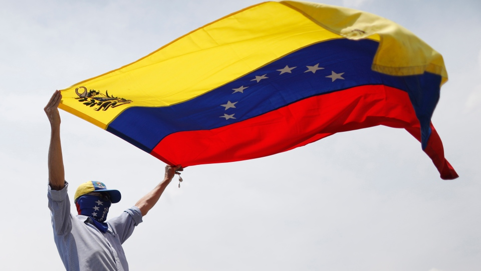 A masked anti-government protester waves a Venezuelan flag during clashes with security forces who fire tear gas from La Carlota airbase in Caracas, Venezuela, Wednesday, May 1, 2019. (AP Photo/Ariana Cubillos)