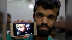 "In this Friday, May 3, 2019 photo, Rozi Khan, a 26-year-old Pakistani shows his picture on his phone next to a picture of the U.S. actor Peter Dinklage who plays Tyrion Lannister on the TV series' ""Game of Thrones,"" in Rawalpindi, Pakistan. (AP Photo/B.K. Bangash)"