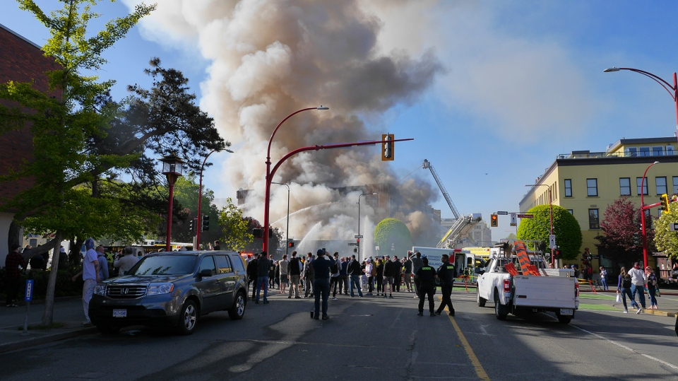 Crowds gather in downtown Victoria to watch a large fire consume the vacant Plaza Hotel Mon., May 6, 2019. (CTV Vancouver Island)