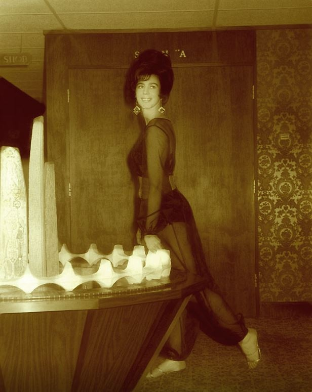 A woman poses inside the Century Inn lobby next to a replica of the Centennial Square fountain. (Glen Mofford)