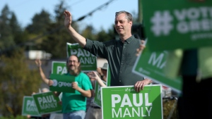 Green party candidate Paul Manly works right up to the end as he takes part in sign waving with supporters near his campaign office before the polls close in the Nanaimo-Ladysmith byelection in Nanaimo, B.C., on Monday, May 6, 2019. THE CANADIAN PRESS/Chad Hipolito