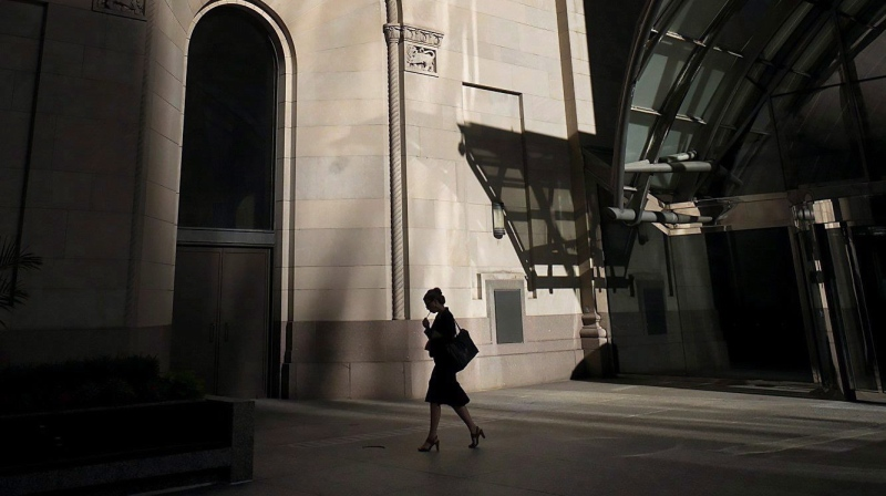 A woman walks through Toronto's financial district on Monday, July 30, 2018. THE CANADIAN PRESS/Graeme Roy