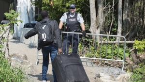 An asylum seeker is confronted by an RCMP officer