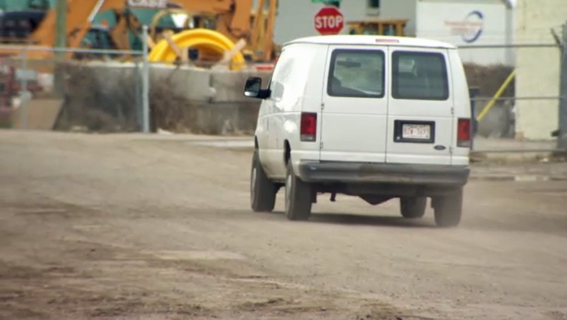 A van churns up dust on Pacific Road N.E., an unpaved road in the Greenview Industrial Park