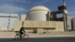 FILE - In this Oct. 26, 2010 file photo, a worker rides a bike in front of the reactor building of the Bushehr nuclear power plant, outside Bushehr, Iran. (AP Photo/Majid Asgaripour/Mehr News Agency, File)