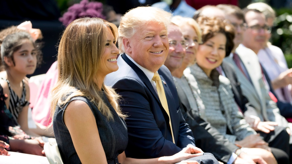 First lady Melania Trump, left, accompanied by U.S. President Donald Trump, center, takes a seat during a one year anniversary event for her Be Best initiative in the Rose Garden of the White House, Tuesday, May 7, 2019, in Washington. (AP Photo/Andrew Harnik)