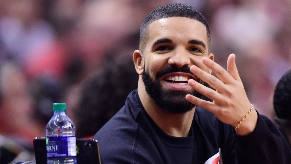 Drake smiles as he sits court at the Toronto Raptors versus Orlando Magic NBA action and watches the Toronto Maple Leafs NHL game on his phone during first half NBA basketball playoff action in Toronto on Tuesday, April 23, 2019. THE CANADIAN PRESS/Frank Gunn