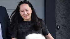 Huawei chief financial officer Meng Wanzhou, back, is accompanied by a private security detail as she leaves her home to attend a court appearance in Vancouver, on Wednesday May 8, 2019. (Darryl Dyck / THE CANADIAN PRESS)