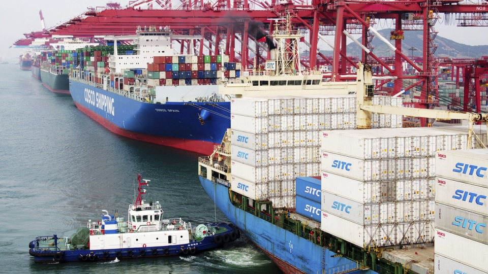 A barge pushes a container ship to the dockyard in Qingdao in eastern China's Shandong province, on May 8, 2019.  (Chinatopix via AP)