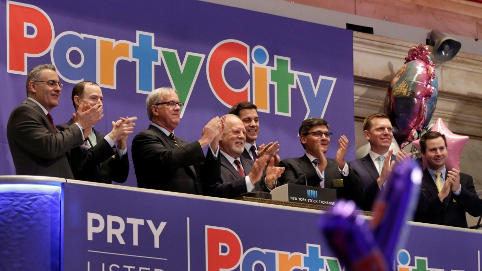 Party City CEO Jim Harrison, third from left, and Chairman Gerry Rittenberg, fourth from left, are joined in applause by company executives during opening bell ceremonies at the New York Stock Exchange, to mark the Party City IPO, Thursday, April 16, 2015. (AP Photo/Richard Drew)