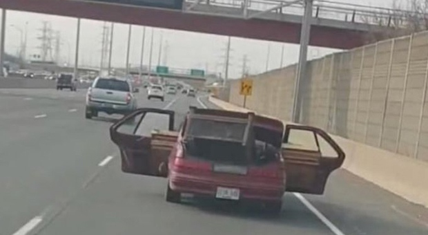 Police have laid charges against a Hamilton man who police allege was spotted driving down the QEW with metal sticking out of the car's open rear doors. (Twitter/ OPP Sgt. Kerry Schmidt)