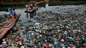In this Sunday, Oct. 2, 2016 file photo, a man guides a raft through a polluted canal littered with plastic bags and other garbage in Mumbai, India. (AP Photo/Rafiq Maqbool, file)