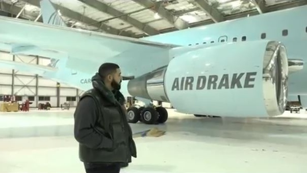 "Drake inspects his new private plane in a hanger as workers unveil the distinctive owl logo and his trademark ""praying hands"" symbol on the tail fin. (Champagnepapi/Instagram)"