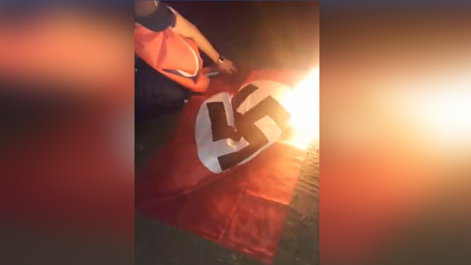 A burning Nazi flag that was hung at a residence in Kelliher, Sask. (Caleb Pelletier)