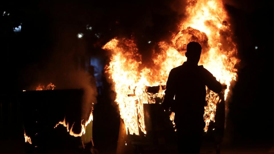 A protester walks in front of burning trash bins during clashes in Tirana, Saturday, May 11, 2019. (AP Photo/Hektor Pustina)