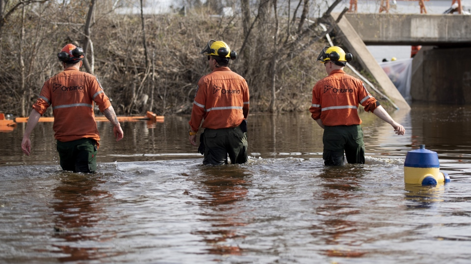 Ontario Ministry of Natural Resources Fire Rangers wade through floodwaters as they deploy pumps in Pembroke, Ont., Saturday, May 11, 2019. (THE CANADIAN PRESS/Justin Tang)