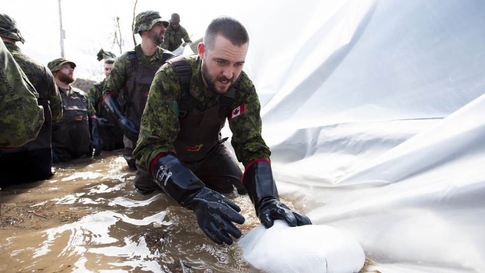 Canadian Forces members build a wall of sandbags at the underpass on Alexander Street to try to keep back floodwaters in Pembroke, Ont., Saturday, May 11, 2019. (THE CANADIAN PRESS/Justin Tang)