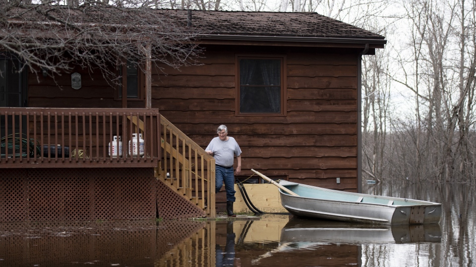 Al Carl stands by the boat that he uses to reach the front door of his seasonal property in the Whitewater Region, east of Pembroke, as flooding continues in the region, on Saturday, May 11, 2019. THE CANADIAN PRESS/Justin Tang